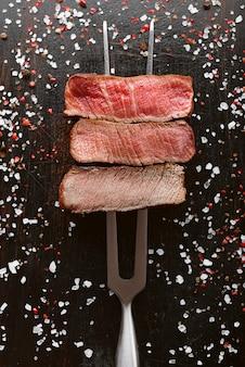 Tre pezzi di carne su una forchetta per carne. tre tipi di arrosti di carne, rari, medi, ben cotti.