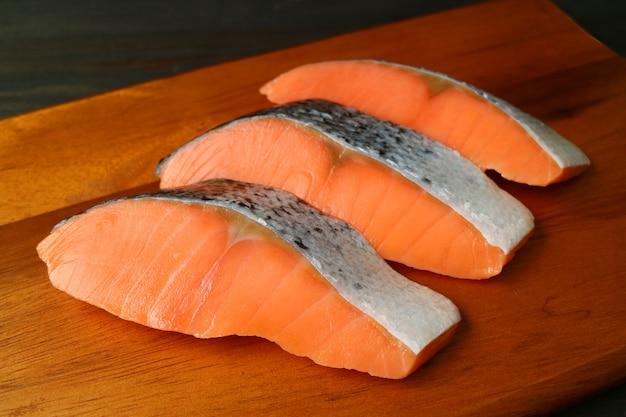 Tre pezzi di salmoni crudi freschi affettati su un tagliere di legno