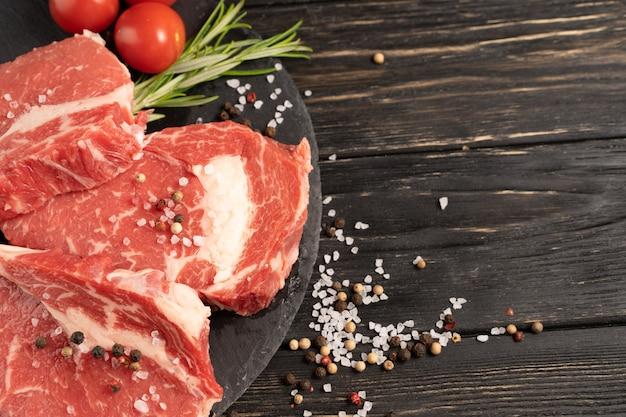 Tre pezzi di succosa carne di manzo cruda su un tagliere di pietra su un tavolo di legno nero.