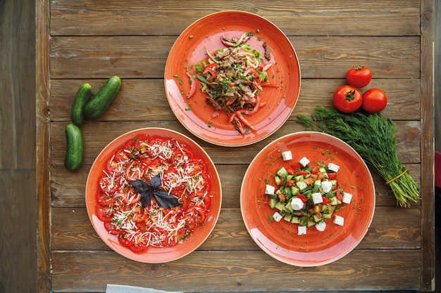 Tre piatti di insalate di verdure in piatti rossi