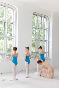 Tre piccole ballerine che ballano con l'insegnante di balletto personale nello studio di danza