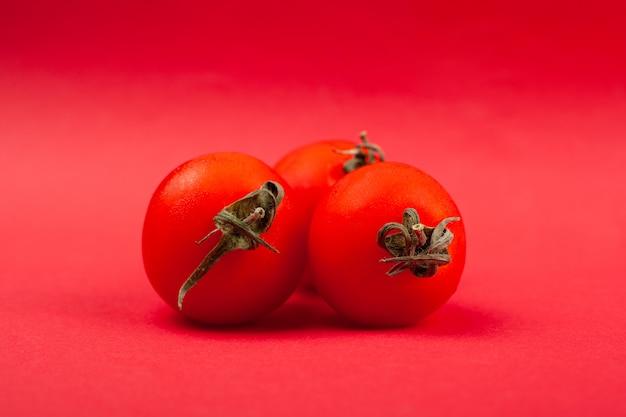 Tre piccoli pomodori succosi rotondi su un primo piano rosso del fondo.