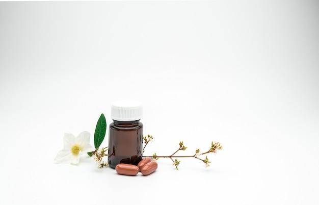 Tre pillole di capsule di vitamina arancione e integratore con fiore e ramo e bottiglia di vetro ambra etichetta vuota su sfondo bianco con spazio di copia, basta aggiungere il tuo testo
