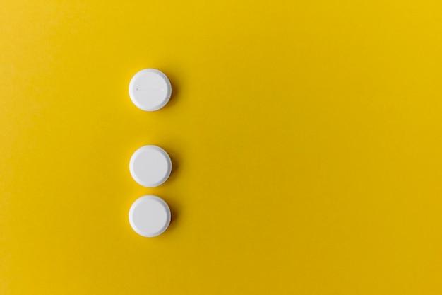 Tre pillole rotonde bianche su giallo
