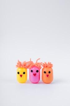 Tre polli fatti di scatole di giocattoli di uova sul tavolo
