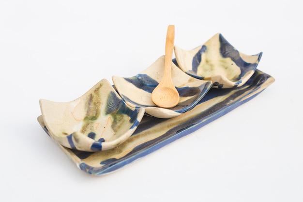 Tre pozzi di gres ceramico e cucchiai di legno con sfondo bianco