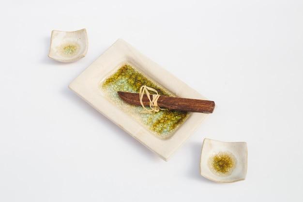 Tre pozzi in gres ceramico e un coltello di legno con sfondo bianco