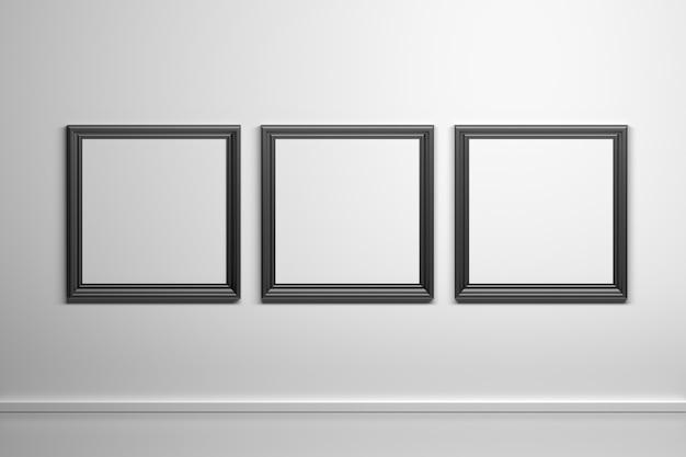 Tre quadrati neri intagliati cornici per foto sul muro bianco
