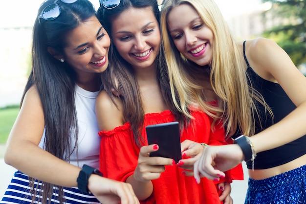 Tre ragazze che chiacchierano con i loro smartphone al parco.