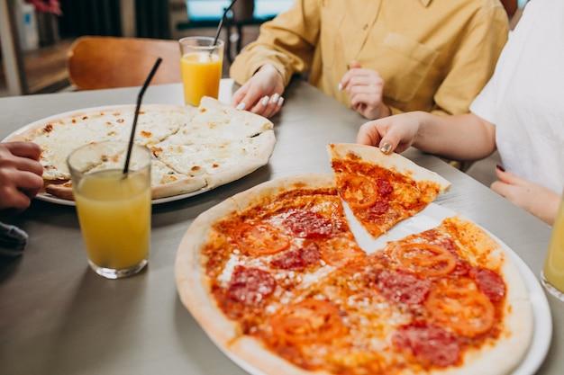 Tre ragazze che mangiano pizza in un bar