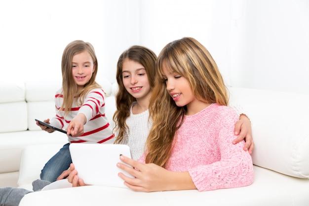 Tre ragazze degli amici della sorella del bambino che giocano insieme al pc della compressa