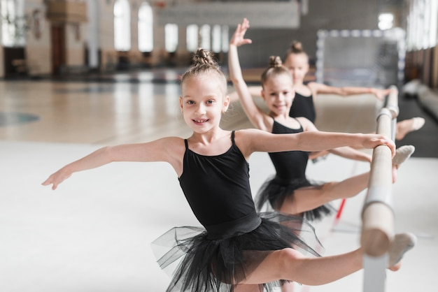 Tre ragazze della ballerina in tutu nero che allunga le loro gambe sulla barra