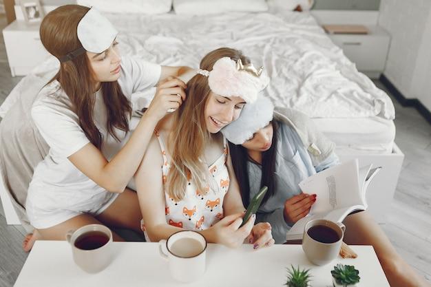 Tre ragazze fanno festa in pigiama a casa