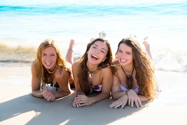 Tre ragazze felici degli amici che si trovano sulla sabbia della spiaggia che sorride