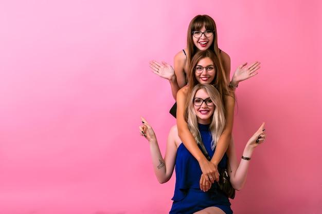 Tre ragazze felici si abbracciano e si divertono insieme, emozioni pazze positive, obiettivi di amicizia, occhiali trasparenti, vestiti luminosi e spazio rosa.