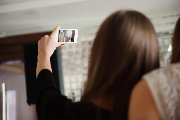 Tre ragazze stanno facendo selfie foto in un ristorante