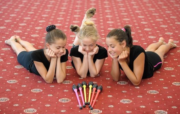Tre ragazze sul pavimento che guardano i club indiani