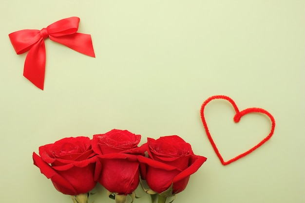 Tre rose rosse con gocce d'acqua su di esse