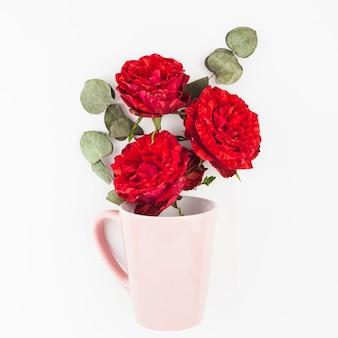 Tre rose rosse con le foglie asciutte nella tazza rosa su fondo bianco