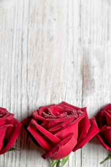 Tre rose rosse su fondo di legno leggero con lo spazio della copia, vista superiore, composizione verticale - immagine