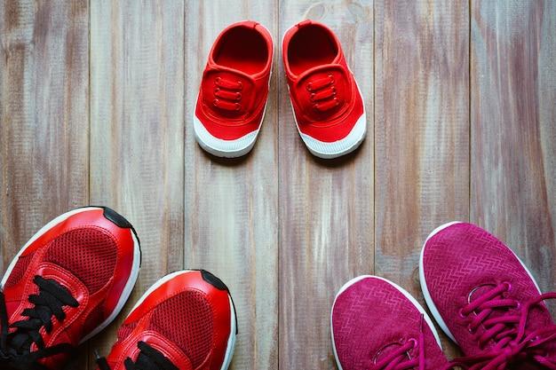 Tre scarpe da corsa sportive rosse o scarpe da ginnastica di madre e padre e figlio