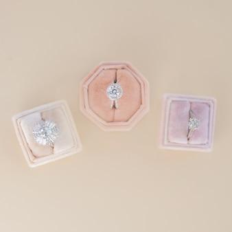 Tre scatole con anelli di fidanzamento si ergono su un tavolo beige