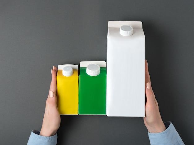 Tre scatole di cartone o imballaggi di tetra pack in mani femminili.