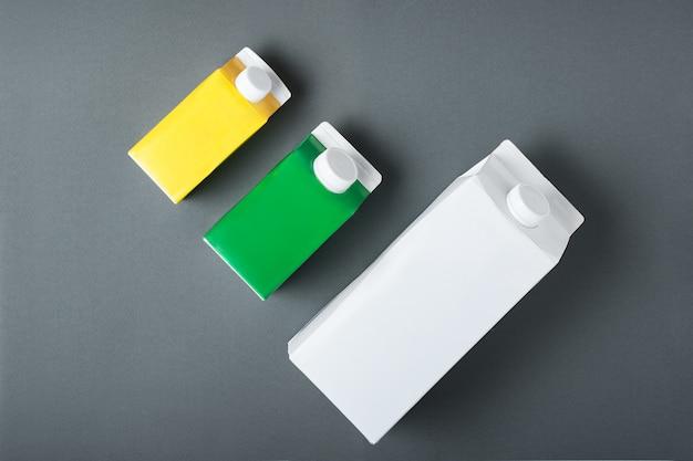 Tre scatole di cartone o imballaggi di tetra pack su nero