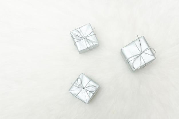 Tre scatole regalo d'argento su uno sfondo bianco