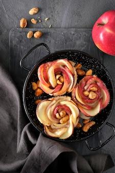 Tre sfogliatine con fettine di mela a forma di rosa cotte in padella di metallo e una mela rossa frizzante