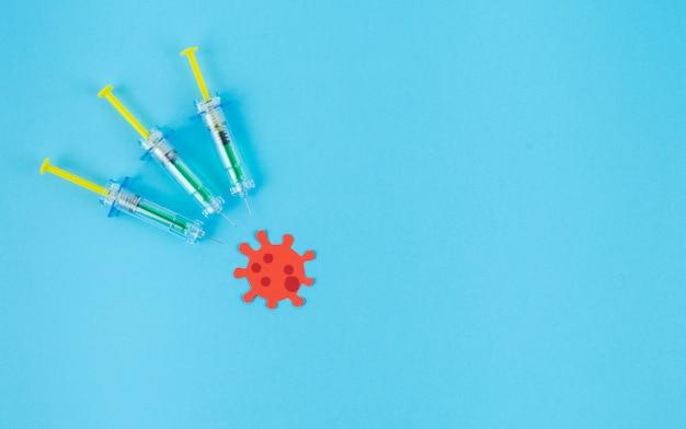 Tre siringhe pungono un virus della carta rossa. concetto covid-19.
