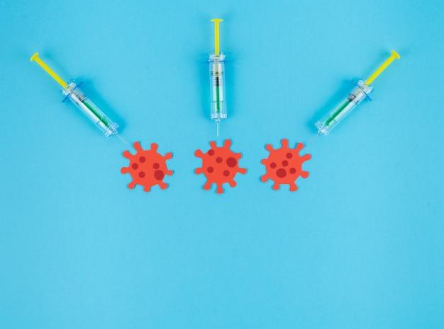 Tre siringhe puntando tre virus rossi ritagliati di carta. concetto covid-19.