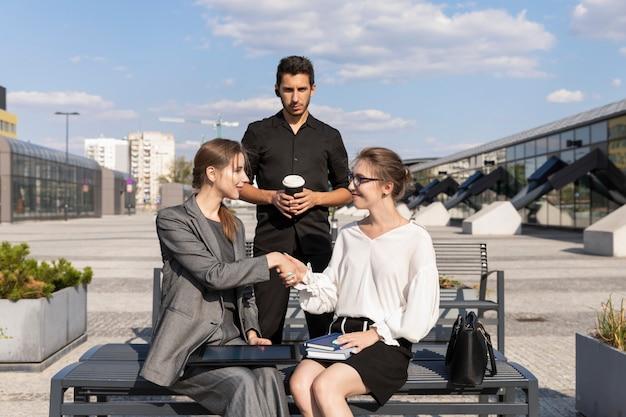 Tre soci d'affari sono in piedi contro un edificio per uffici. si stringono la mano, come segno di negoziati di successo.