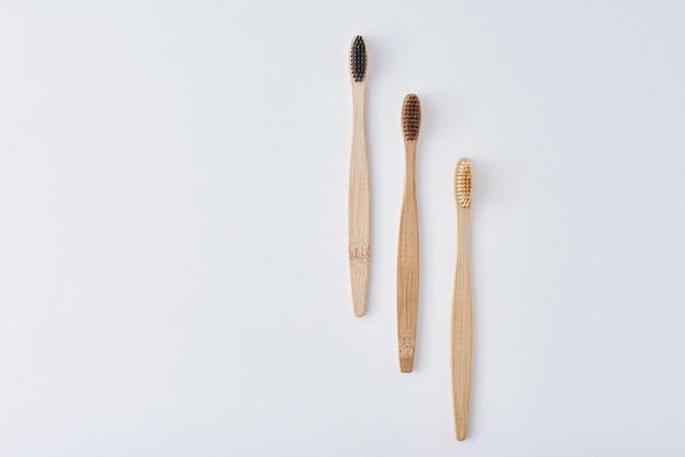 Tre spazzolini da denti di bambù di legno su una vista bianca e superiore. concetto di cura dentale