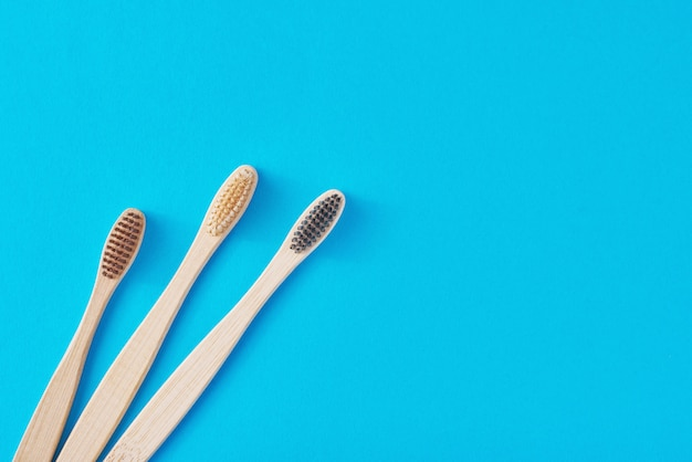 Tre spazzolini da denti in legno di bambù su una vista blu e superiore. concetto di cura dentale