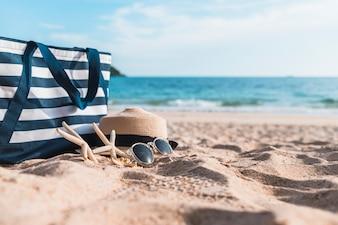 Tre stelle marine con borsa blu sulla sabbia