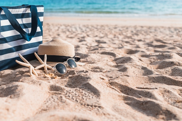 Tre stelle marine con grande borsa sulla sabbia