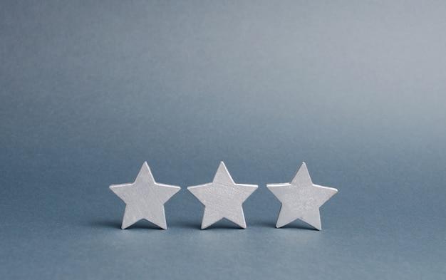 Tre stelle su un grigio. il punteggio dell'hotel, del ristorante, dell'applicazione mobile