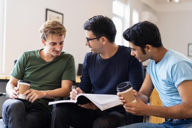 Tre studenti che leggono insieme il libro di testo, parlano e bevono