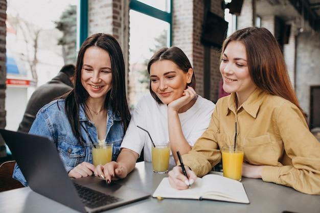 Tre studenti che si preparano per l'esame con il computer portatile in un caffè