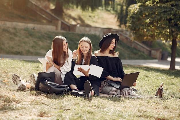 Tre studenti seduti su un prato con il portatile