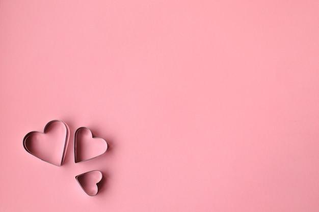 Tre tagliabiscotti a forma di cuore sopra il rosa. san valentino.
