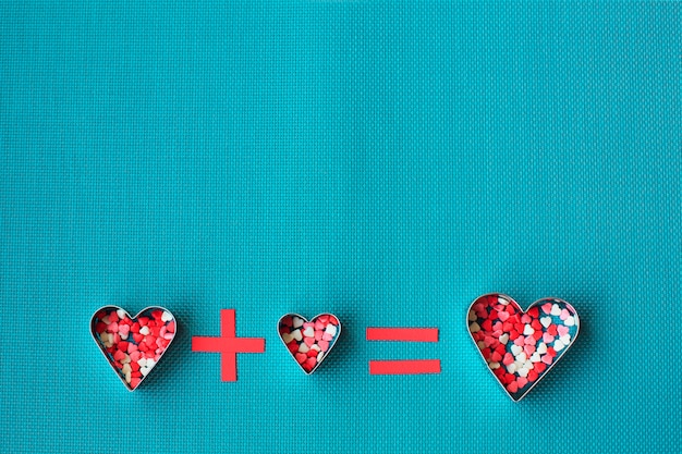 Tre tagliabiscotti a forma di cuore sopra un blu.