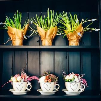 Tre tazze bianche con fiori sullo scaffale.
