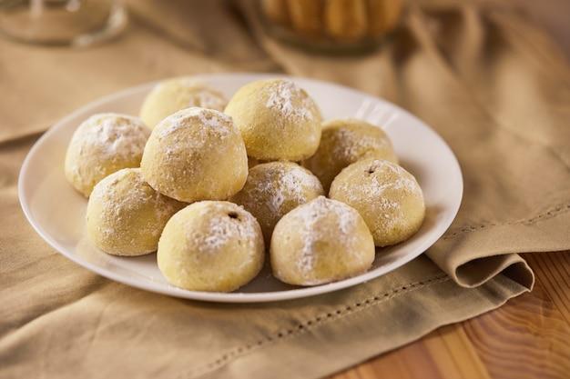 Tre tipi di biscotti nei toni del beige su un tovagliolo in un piatto e in un barattolo. il concetto di uno stile rustico
