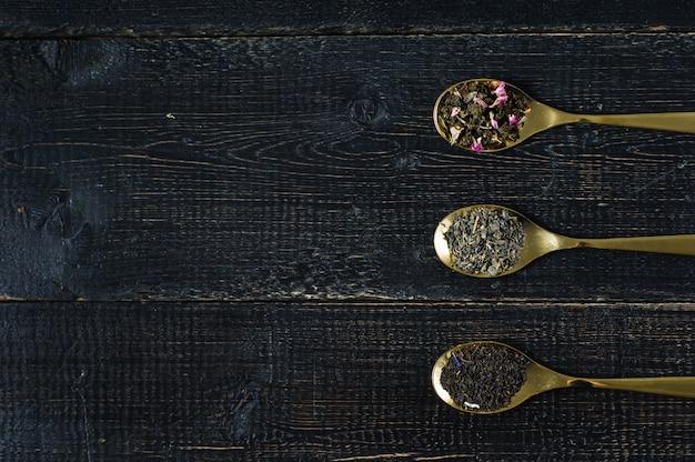 Tre tipi di tè in cucchiai: verde, nero e rooibos