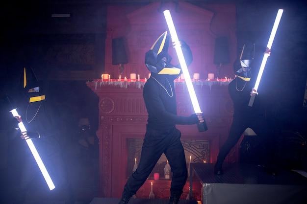 Tre uomini in maschere da lupo ballano con le lampadine nel club