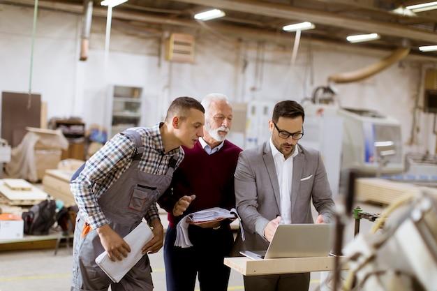 Tre uomini in piedi e discutono nella fabbrica di mobili