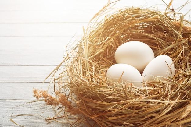 Tre uova bianche nel nido di fieno