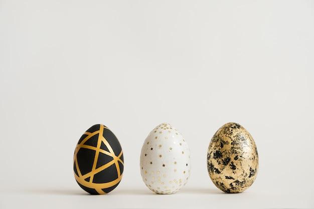 Tre uova decorate dorate di pasqua. concetto di pasqua minimo